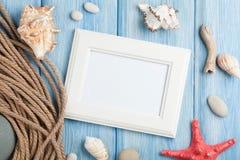 Havssemestern med den tomma fotoramen, stjärnafisken och flottan rope Arkivbild