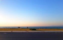 Havssikt från vägen för solnedgång med en tom bänk Arkivbild