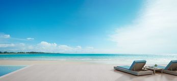 Havssiktssimbassäng bredvid terrass och sängar i modernt lyxigt strandhus med bakgrund för blå himmel, vardagsrumstolar på trädäc arkivfoto
