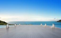 Havssiktssimbassäng och tom stor terrass i modernt lyxigt strandhus med bakgrund för blå himmel, lampor på stort trädäck arkivbilder