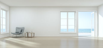 Havssiktsvardagsrum med den tomma väggen i det moderna strandhuset, lyxig vit inre av sommarhemmet Arkivbild