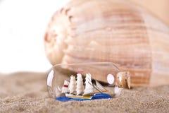 Havsskal och skepp i flaskan på stranden Royaltyfri Bild