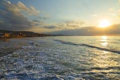 Havsskum på kust för sandig strand under härlig himmel på solnedgången med avlägsna klippor och semesterorthotell crete greece Royaltyfri Bild