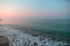 Havsskum på stranden sätta på land soluppgången royaltyfria bilder