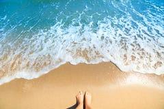 Havsskum, vågor och den nakna foten på en sand sätter på land royaltyfri fotografi