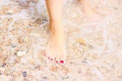 Havsskum, v?gor och den nakna foten p? en sand s?tter p? land Ferier kopplar av royaltyfria foton