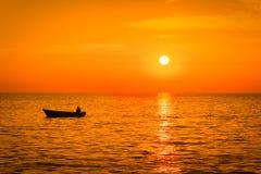 Havssolnedgång med en fishermansfartygkontur Arkivbilder