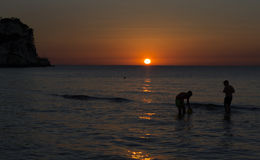 Havssolnedgång med pojkar royaltyfria foton