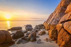 Havssolnedgången vaggar stranden på bakgrund för blå himmel Skönhetaftonsoluppgång background card congratulation invitation royaltyfri foto