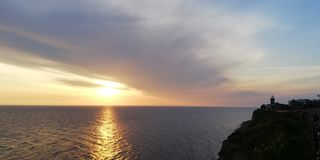 Havssolnedg?nglandskap i bl?a och guld- signaler P? yttersidan av havet mousserar den sol- banan Fyren royaltyfria bilder