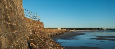 Havsvägg vid fjärden Jersey för ` s för St Ouen i lågvatten Royaltyfria Bilder