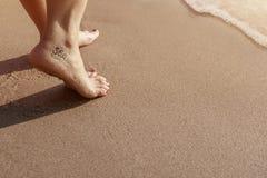 Havsvänkvinna med tatueringen som går på sandstranden under solnedgång Royaltyfri Bild