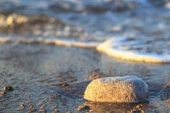 Havsvåg på sand och stenen på soluppgång Royaltyfri Fotografi