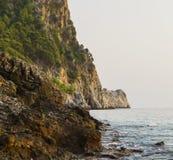 Havsvågor kraschar till vaggar klippan, och grottor nära sjösidan med kullar som täckas med naturlig landskapseascape för skog, b arkivbilder