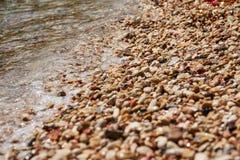 Havsvågor med många härliga strandkiselstenar texturerar bakgrund Sätta på land med vit, guling, och grå färg stenar slappt runda royaltyfri bild