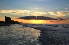 Havsvågor mousserar nedanför resningsolen på den kust- shorelinen för havet Royaltyfria Bilder