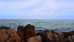 Havsvågor och stenig kust arkivfilmer