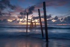 Havsvågor piskar linjen inverkan på sandstranden med gammal wood bridg fotografering för bildbyråer