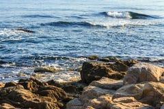 Havsvågor rusar upp near kust- klippor Arkivbilder