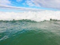 Havsvågor som når att svepa till kusten arkivfoton