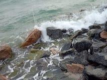 Havsvågor som onshore kraschar stenar arkivbild