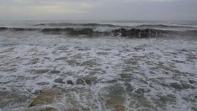 Havsvågor som slår mot, vaggar av pir arkivfilmer