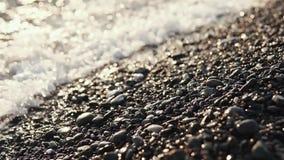 Havsvågor tvättar grusstranden, närbild i solnedgångtid stock video