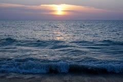 Havsvågorna slår kusten/stranden på solnedgången Arkivfoto