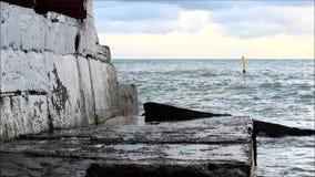 Havsvågorna slår mot den konkreta pir arkivfilmer