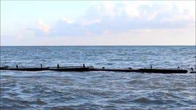 Havsvågorna slår mot den skyddande kust- strukturen för deras återbetalning i stormen stock video