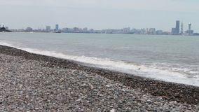 Havsvågtakt på stenig kust på invallningen av den georgiska staden av semesterorten av Batumi lager videofilmer