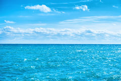 Havsvatten och blå himmel med vita moln Arkivbild