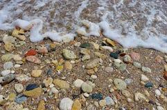 Havsvatten och färgade stenar Arkivfoto