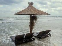 Havsvatten på sjösidan med sunbeds och sugrörparaplyet, sand och blå himmel, molnig dag Royaltyfria Foton
