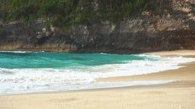 Havvåg på den tropiska stranden Vitt sand- och kristall-blått hav Kelingking strand Nusa Penida stock video