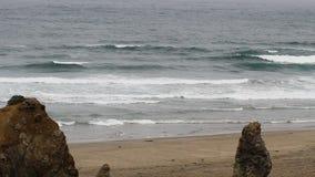 Havvågor på sandstranden med stort vaggar Kalifornien arkivfilmer