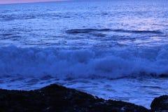 Havvågor på solnedgången Arkivfoto