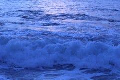 Havvågor på solnedgången Arkivfoton