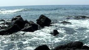 Havvågor på svarta Lava Rock Kona Hawaii lager videofilmer
