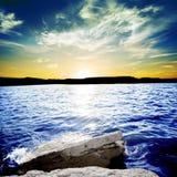 Havvågor som bryter på en vagga med solnedgång arkivbild