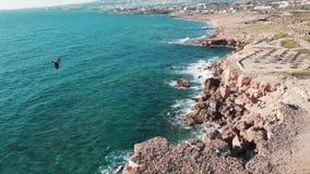 Havvågor som kraschar och slår på steniga klippor, sätter på land Flyg- sikt av den steniga kusten Fågelflyg över kustlinjen Surr stock video