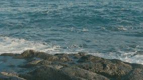 Havvågor som kraschar på den vulkaniska stenstranden arkivfilmer