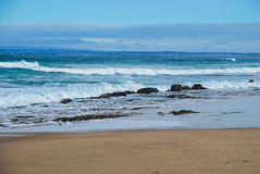 Havvågor som rullar till den sandiga stranden, invånareland på bakgrunden Havdunge, Victoria, Australien Royaltyfria Foton
