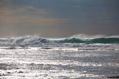 Havvågor stänger sig upp och gnistrandet av vatten på solnedgången royaltyfri bild