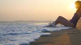 Havv?gor som tv?ttar sig ?ver brunbr?nd kvinnlig kropp Gullig flicka som ligger på stranden i vågorna på solnedgångtid h?rligt ba stock video