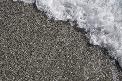 Havvatten som svaller in över sandstranden Nice färger och detaljer Arkivfoto