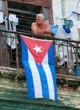 HAWAŃSKI, CUBA-JULY 26,2006: Mężczyzna pozycja na balkonie z Kubańską flaga Zdjęcia Royalty Free