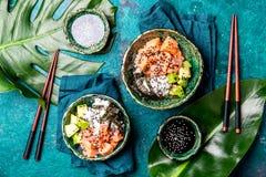 Hawaiansk laxpoce med avokadot, ris och sesamo tjänade som i bunkar på tropiska sidor Turkos kritiserar bakgrund överkant Royaltyfria Bilder