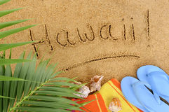 Hawaii beach palm tree. Hawaii beach writing : Hawaii beach background with palm leaves, towel and flip flops Royalty Free Stock Images