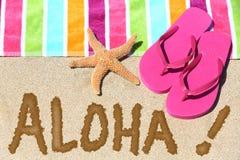 Hawaii beach travel concept - ALOHA. Hawaii beach travel concept. ALOHA text written in sand with water next to beach towel and summer sandals and starfish Royalty Free Stock Photos